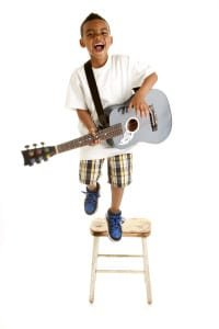 Little Boy Performs a Song with Guitar